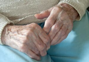 Elderly woman holding her painful arthritic fingers in Flowery Branch, Georgia