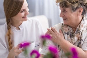 Young Caregiver Shares a Cup of Coffee with a Senior Woman in Flowery Branch, Georgia