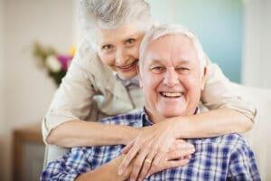Portrait of senior woman embracing man in living room in Flowery Branch, Georgia.