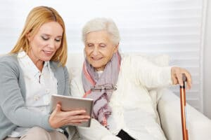 Woman giving senior woman introduction to a tablet in Flowery Branch, Georgia